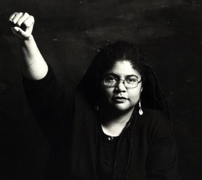 A photo of Linda Thurston, a Black woman with dreadlocks, her right fist raised